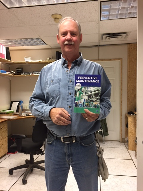 """Photo of Doug showing his book, """"Preventive Maintenance"""""""